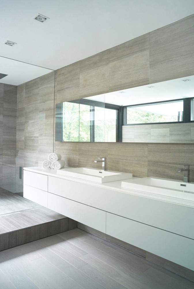 a neutral bathroom clad with wood like tiles, with a sleek floating vanity, a long mirror and some square sinks
