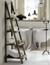a neutral shabby chic bathroom with a clawfoot tub, a windowsill shelf, a ladder, a candleholder and vintage lamps