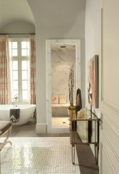 a refined and luxurious neutral bathroom clad with marble and marble tiles, an oval tub, vintage furniture and printed textiles