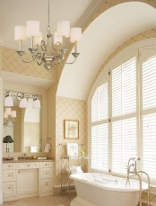 a neutral and warm-colored bathroom with a glazed wall, a vintage tub, a vintage chandelier, a built-in vanity and a mirror