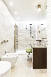 a neutral contemporary bathroom with a dark vanity and glass sinks, white appliances, a shower space and neutral stone tiles
