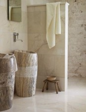 a refined neutral bathroom with mismatching tiles, free-standing sinks carved out of stone, a shower space and a mirror