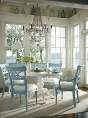 a vintage neutral and pastel sunroom with glazed walls, a white round table and powder blue chairs and an aqua sideboard plus bottles on display