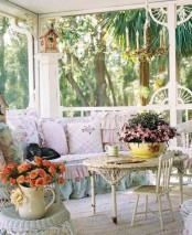 a vintage to shabby chic sunroom with chic neutral furniture, floral upholstery, elegant chadeliers and lots of blooms