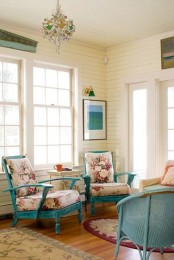 a vintage coastal sunroom with blue furniture, floral upholstery, a bright chandelier and an artwork
