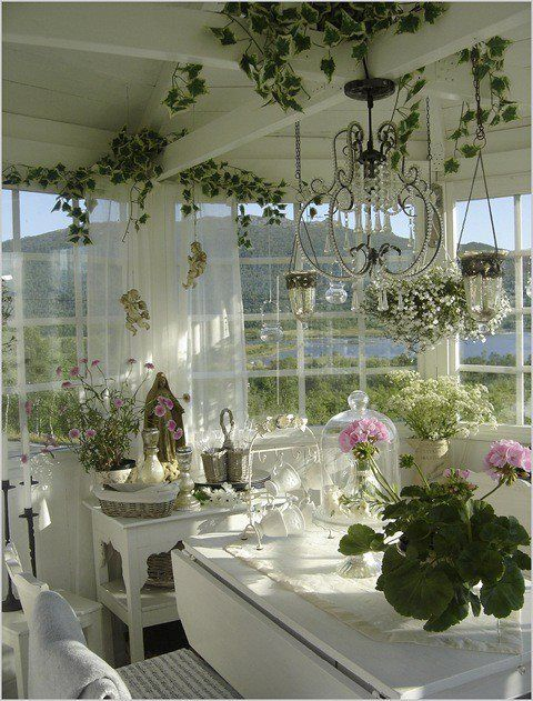 a charming neutral sunroom with crystal chandeliers and lamps, with potted blooms and greenery and a lovely view