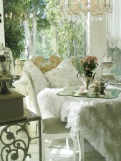 a refined white vintage sunroom with shabby chic and vintage furniture, a crystal chandelier, floral pillows and blooms in vases