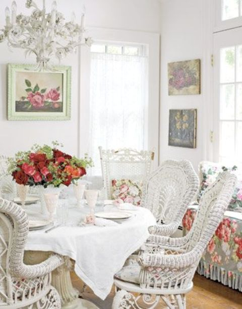 a white vintage sunroom with white wicker furniture, floral textiles, floral artworks and a chic white chandelier