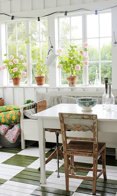 an eclectic vintage sunroom with shabby chic and vintage furniture, white and stained, colorful textiles and potted blooms