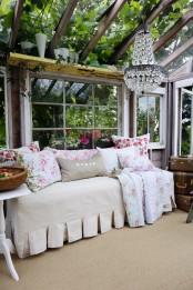 a chic vintage sunroom with greenery all around, a crystal chandelier, neutral furniture and floral textiles