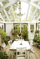 an elegant vintage sunroom with a glazed ceiling, white vintage furniture, a crystal chandelier, potted greenery and blooms looks refined