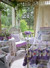 a chic and girlish vintage sunroom with elegant white forged furniture, purple and lavender textiles, lots of potted greenery and blooms