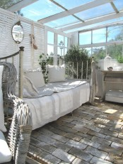 a vintage white sunroom with shutters, neutral forged and wicker furniture, potted greenery and a cage for decor