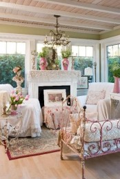 a refined vintage sunroom in neutrals and pastels, with a non-working fireplace, a crystal chandelier, floral textiles, blooms in pots and vases and gorgeous views