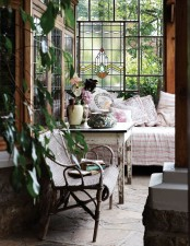 a vintage to shabby chic sunroom with elegant wooden and wicker furniture, pastel textiles, potted greenery and blooms and pastel floral textiles
