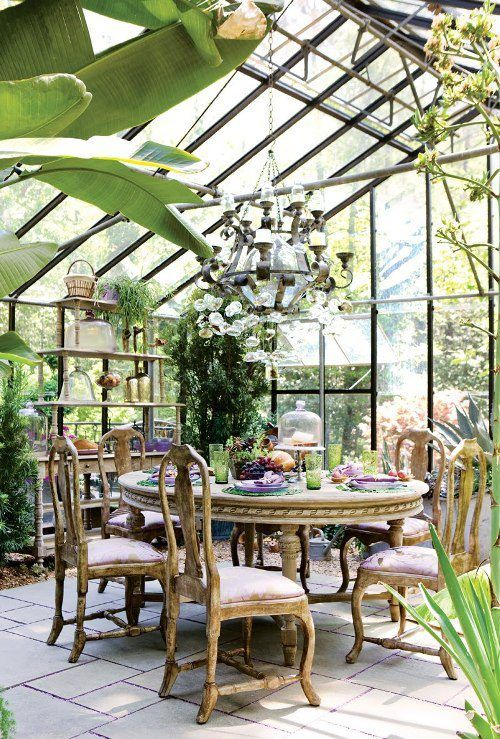 a bright vintage sunroom with refined wooden furniture, an oversized chandelier and potted greenery, colorful textiles
