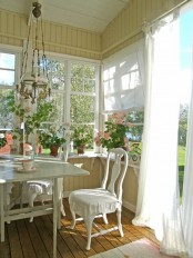 a buttermilk colored vintage sunroom with elegant white furniture, a vintage chandelier and lots of potted blooms on the windowsills