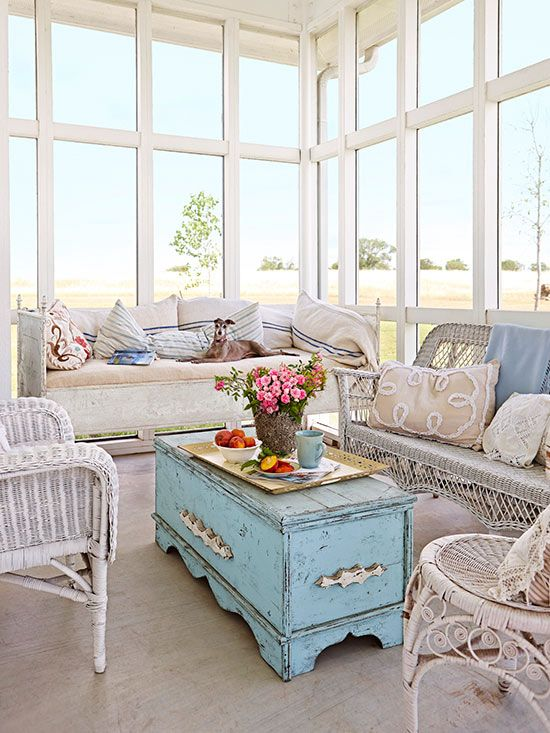 a vintage sunroom with all glazed walls, white wicker furniture, a blue shabby chic chest, printed and embroidered pillows and blooms in a vase
