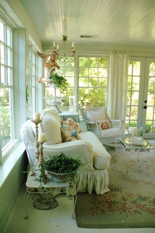a vintage and shabby chic sunroom in white, with neutral upholstered furniture, wicker chairs, elegant vintage tables and floral pillows