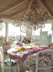 a luxurious vintage sunroom with windows all around, crystal chandeliers, refined furniture and floral chairsfloral artworks