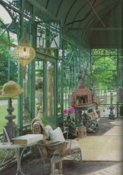a vintage blue green sunroom with elegant and refined blue garden furniture, elegant candle holders and lanterns, a crystal chandelier is welcoming