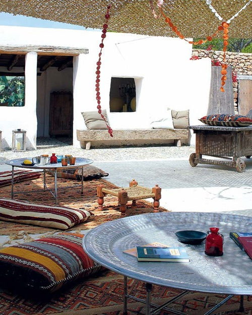 a bright Moroccan patio with colorful printed rugs and pillows, low metal tables and colorful glasses