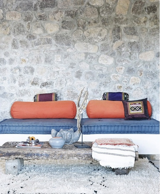 a bright Moroccan patio in navy and orange, with a low table on wheels and bright textiles