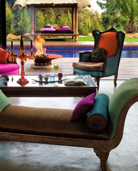 an elegant and colorful Moroccan meets luxurious patio with bright furniture and pillows, a fire pit and a candelabra