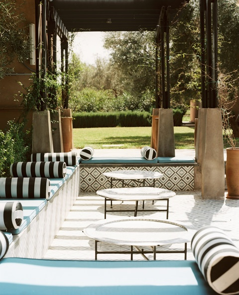a black and white striped patio with touches of turquoise and low coffee tables