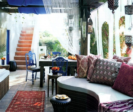 a bright Moroccan space with a curved sofa, Moroccan lanterns over it, a wooden table and bright blue chairs