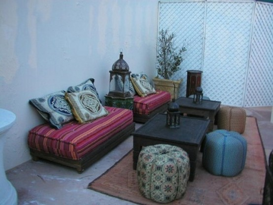 a bright Moroccan patio with colorful furniture, leather ottomans and a low coffee table