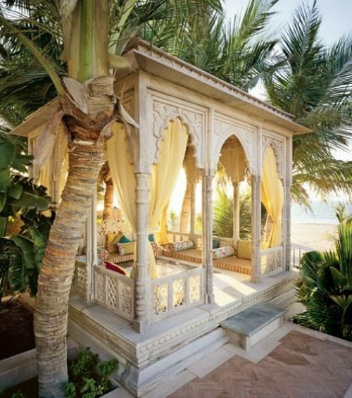 a white Moroccan cabana of carved wood with a long upholstered bench and bright pillows