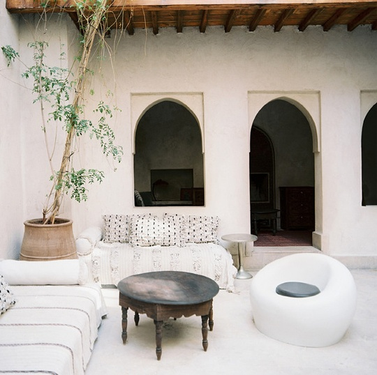 a white Moroccan patio with contemporary furniture, a low wooden table and potted greenery