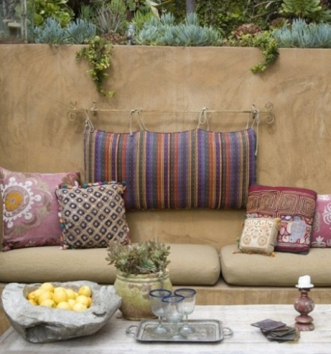 a simple Moroccan patio with colorful pillows, potted greenery and stone decor