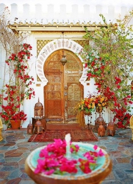 a colorful Moroccan space with lots of rugs, Moroccan lanterns and a fountain with petals