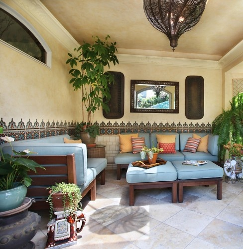 mosaic tiles on the walls, blue upholstered furniture, Moroccan lanterns and potted greenery
