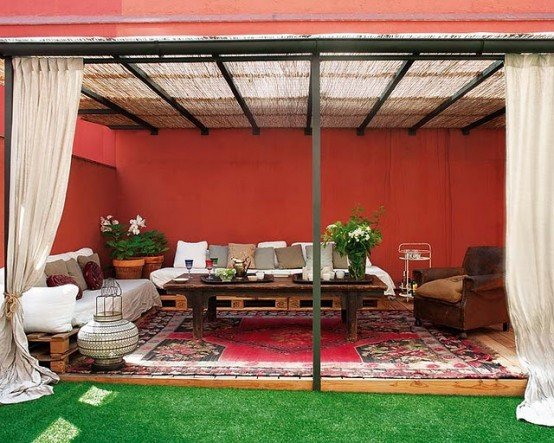 a bright red patio with curtains, pallet sofas and a table plus Moroccan rugs and lanterns