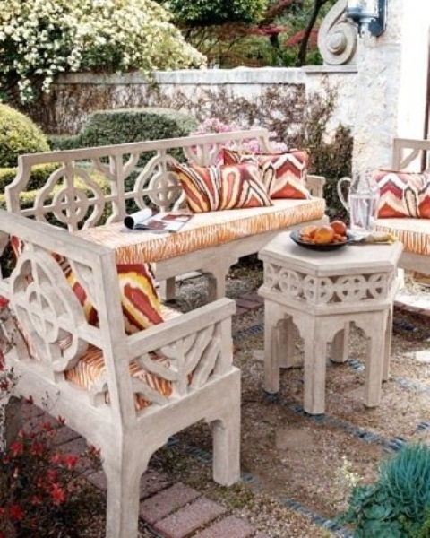 a cozy Moroccan patio with white carved furniture and bright textiles