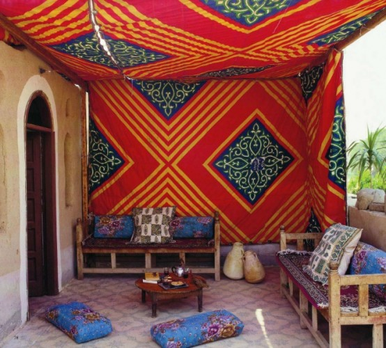 a bright Moroccan space done in blue and red, with patterns and comfy furniture