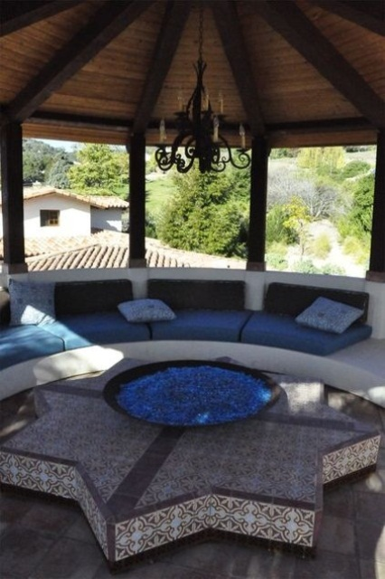 a roofed Moroccan patio done with a rounded bench, a star-shaped stand and a fire pit