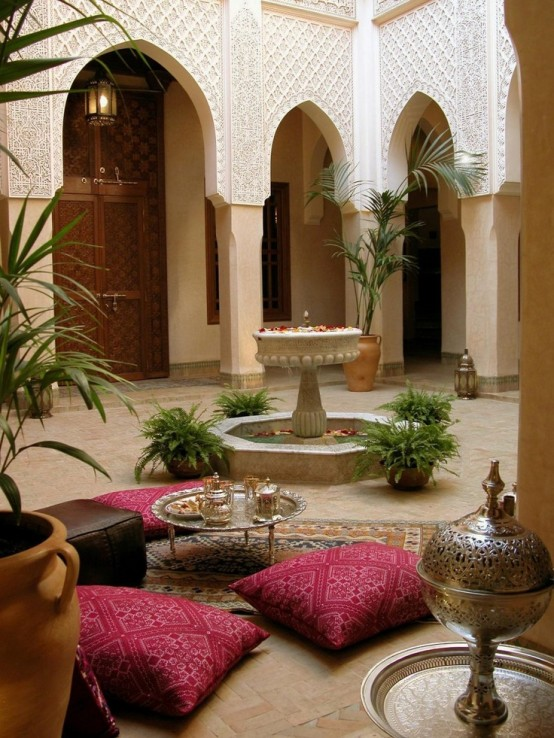 a cozy Moroccan patio with pink pillows, a fountain and potted greenery, low furniture and ottomans