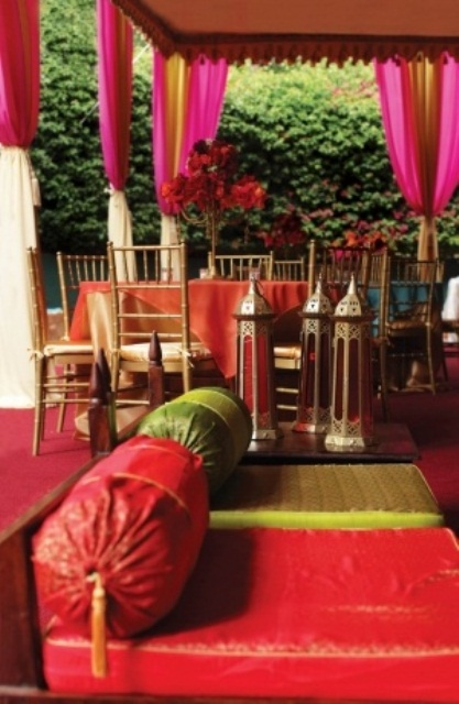 a pink, red and green Moroccan patio with lanterns, bright pillows and curtains