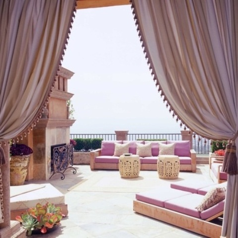 a colorful Moroccan patio with bright pnk textiles, carved siddde tables and touches of ivory