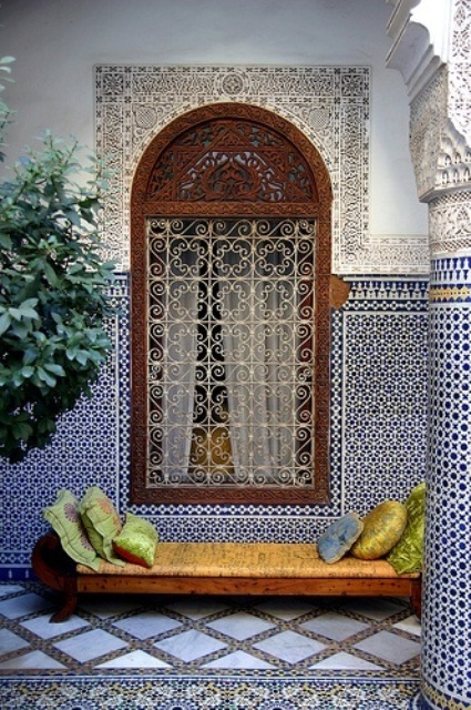 a Moroccan patio clad with mosaic blue and white tiles, a carved window frame and a bright daybed
