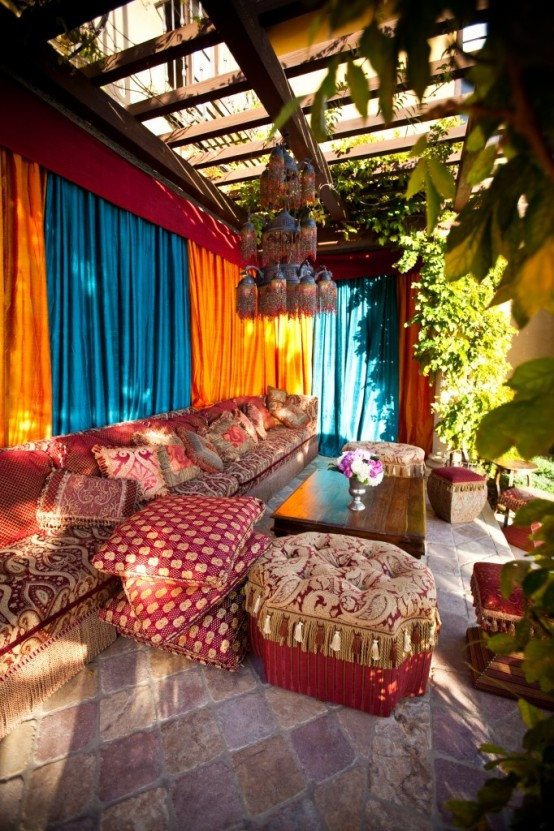 a super bright Moroccan patio with colorful curtains, bright textiles and pillows and a large chandelier