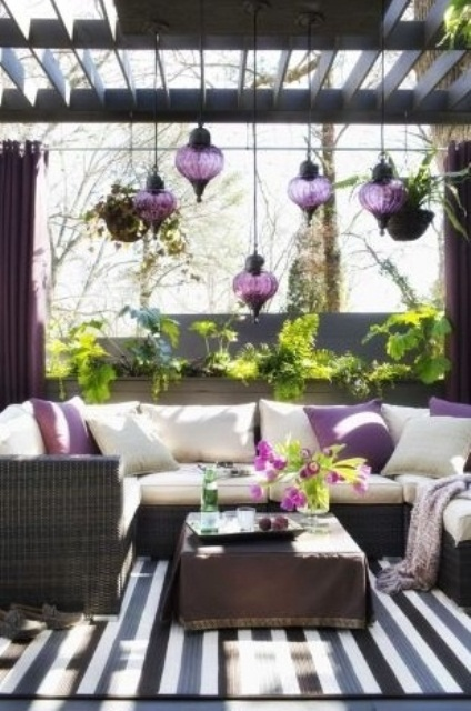a chic terrace done in dark shades and white and with purple Moroccan lanterns over it