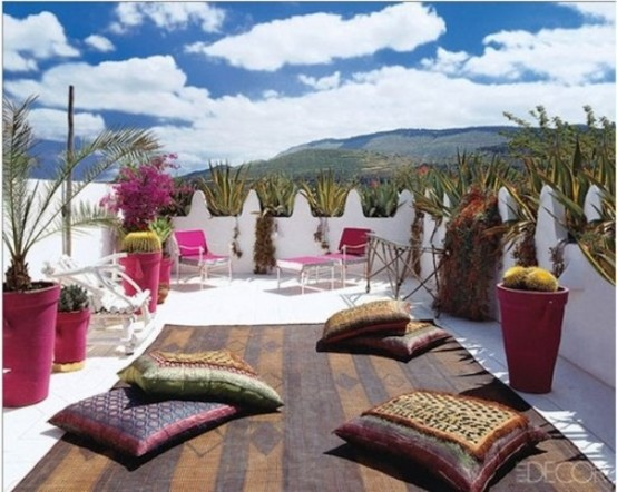 a bright rooftop terrace with greenery in colorful pots, pink loungers and colorful textiles