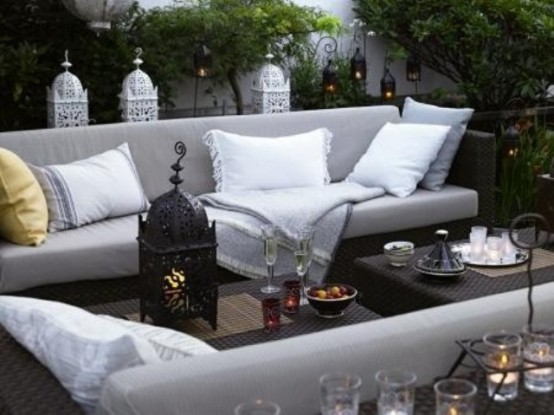 a neutral terrace decorated with Moroccan lanterns and comfy contemporary furniture