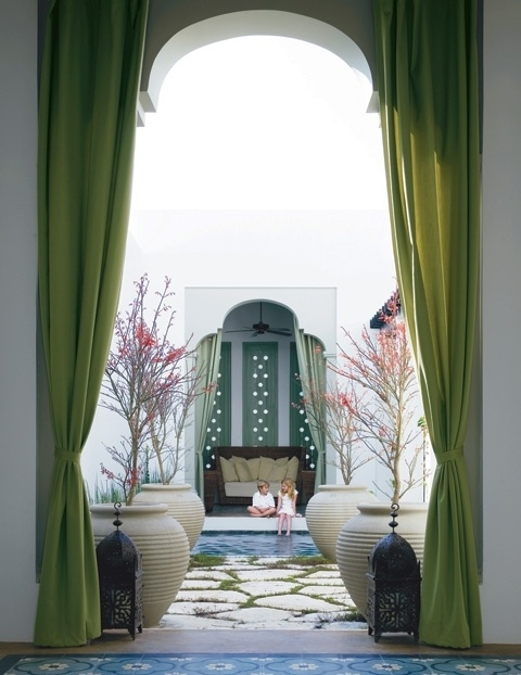 a Moroccan space with grene curtains, Moroccan lanterns and potted trees