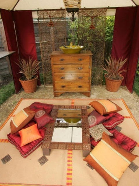 a warm-colored Moroccan patio in sandy beige and red, with pillows, rugs and a low table with a mirror in the center
